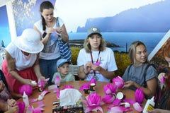 符拉迪沃斯托克,俄罗斯, 2017年9月, 10日 参与在主要类`的人们如何由纸`做莲花在PR 免版税库存照片