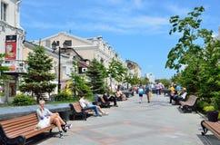 符拉迪沃斯托克,俄罗斯, 2016年6月, 01日 妇女坐在Fokin海军上将星期二街道上的长凳和谈话在手机 免版税库存图片