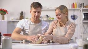 笨拙地揉面团的愉快的夫妇,一起花费乐趣时间在厨房里 股票录像