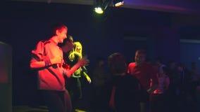 笨拙跳舞在迪斯科舞厅的少年进入小农村俱乐部阶段 红色聚光灯 兴奋 股票录像