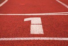 第一….并且优胜者是超级商人! 在红色橡胶跑马场的白色轨道数字,连续跑马场纹理在体育场内 免版税库存图片