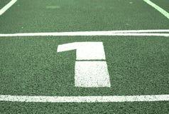 第一….并且优胜者是超级商人! 在红色橡胶跑马场的白色轨道数字,连续跑马场纹理在体育场内 免版税库存照片