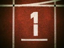 第一….并且优胜者是超级商人! 在红色橡胶跑马场的白色轨道数字,连续跑马场纹理在小室外体育场内 免版税库存图片