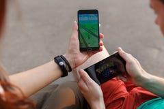 第一个人在显示的手上拿着电话它的有Pokemon的屏幕去app,其次安装那种应用 免版税库存图片