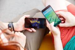 第一个人在显示的手上拿着电话它的有Pokemon的屏幕去app,其次安装那种应用 免版税库存照片