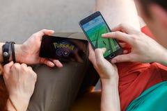 第一个人在显示的手上拿着电话它的有Pokemon的屏幕去app,其次安装那种应用 图库摄影