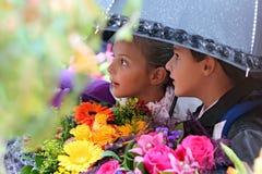 第一个平地机女孩和男孩在一把伞下在学校 库存图片
