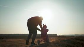 第一个教训骑自行车骑马 学会年轻的男孩骑自行车,父亲教他的儿子骑在日落的一辆自行车 股票录像