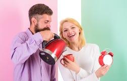 第一件事他们每天早晨准备热的饮料 一起享受好早晨 有电水壶的男人和妇女 免版税库存图片