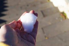 第一冷的雪在温暖的手上 免版税库存照片