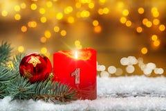 第一出现,装饰用蜡烛、球和冷杉在雪 免版税库存照片