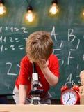 第一前对学习感兴趣,学会,教育 孩子男孩调查显微镜在教室,黑板  免版税库存图片