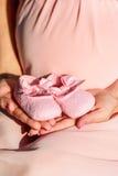第一双女婴鞋子在父母手上 图库摄影