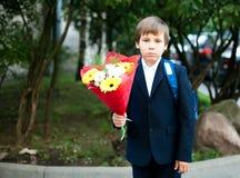 第一天在学校,有花的男孩 库存图片