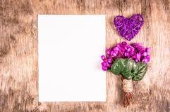第一朵春天花和柳条心脏在一个木板 花和空白的纸片 浪漫概念 免版税库存图片