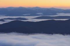 第一棵草高薄雾早晨山峰发出光线多雪的星期日 库存照片