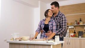 第一次烹调在他们新的家的年轻已婚夫妇 库存图片