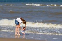 第一次照顾和她新出生的女儿海滩的 免版税库存照片