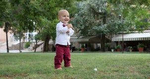 第一步慢动作录影镜头孩子,走他自己赤足在绿草的可爱的小孩 影视素材