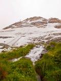第一雪在阿尔卑斯旅游区域 有急流小河的新鲜的绿色草甸 阿尔卑斯山峰顶在背景中 库存图片