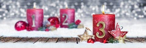 第三星期天与金黄金属在木板条的第一的出现红色蜡烛在银色bokeh背景雪前面  库存照片