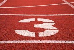 第三 在红色橡胶跑马场的白色轨道数字,跑马场纹理在体育场内 库存图片