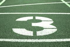 第三 在红色橡胶跑马场的白色轨道数字,跑马场纹理在体育场内 免版税图库摄影