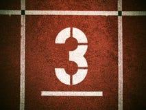 第三 在红色橡胶跑马场的白色轨道数字,连续跑马场纹理在运动体育场内 库存图片