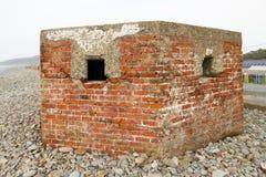 第二次世界大战药盒pebbled海滩, Fairbourne 免版税库存照片