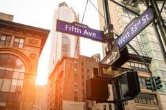 第五个Ave和西部第33个St的路牌在日落在纽约 免版税库存照片
