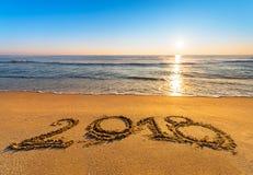 第在海滨沙子写的2018年在日出 免版税库存照片
