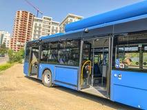 第比利斯,乔治亚- - 2018年5月17日:对公共汽车停车处的城市蓝色公共汽车,以新的大厦为背景 免版税库存照片
