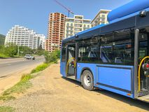第比利斯,乔治亚- - 2018年5月17日:对公共汽车停车处的城市蓝色公共汽车,以新的大厦为背景 库存图片