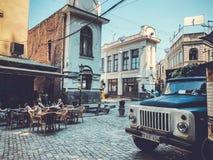 第比利斯,乔治亚- 2018年7月10日:老镇街道,在Shardeni街道的咖啡馆 老货物汽车的前面 免版税库存照片