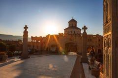 第比利斯,乔治亚- 2016年10月8日:在主要门入口的日落对最大第比利斯Sameba大教堂的三位一体的视图和十字架 免版税库存图片