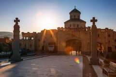 第比利斯,乔治亚- 2016年10月8日:在主要门入口的日落对最大第比利斯Sameba大教堂的三位一体的视图和十字架 库存图片