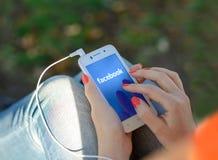 第聂伯罗彼得罗夫斯克,乌克兰- 2014年9月18日:使用在巧妙的电话的少妇Facebook社会网络应用 库存图片