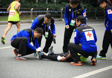 第2位国际马拉松运动员受了伤,帮助的志愿者舒展他的脚 免版税库存图片