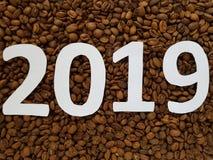 第2019年在白色用烤咖啡豆背景,设计新年 库存照片