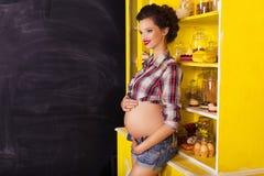 第7次月怀孕的美丽的深色的妇女在格子花呢上衣 免版税库存图片