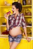 第7次月怀孕的美丽的深色的妇女在格子花呢上衣 免版税库存照片