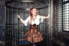 笼子的叫喊的美丽的steampunk妇女 免版税库存照片
