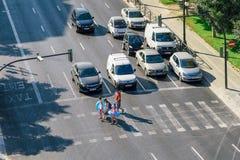 等在红绿灯的汽车步行者穿过街道 免版税库存图片