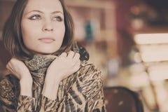 等待一杯茶在咖啡馆的一个年轻美丽的女孩 免版税库存照片