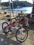 等待他们所有者在海滩附近的两辆出租自行车 免版税库存图片