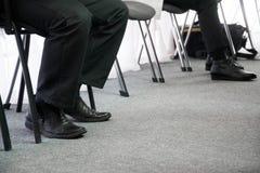 等待他们的轮办公室椅子的人的腿在走廊 采访和工作查找 库存图片