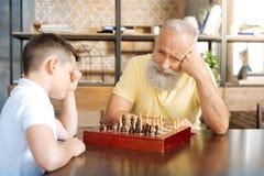 等待他的在下棋比赛的祖父孙子接下来的步骤 库存图片