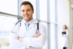 等待他的队的微笑的医生,当站立挺直时 免版税库存照片