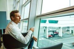 等待他的飞行的白色衬衫的年轻愉快的商人 免版税库存照片