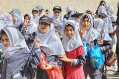 等待伊朗的女小学生开始游览在堡垒墙壁  免版税库存照片
